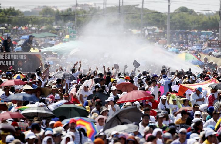 Firefighters spray water on pilgrims to cool them down before Pope Francis arrives to lead a mass at the Los Samanes park in Guayaquil, Ecuador, July 6, 2015. Pope Francis landed in Ecuador's capital Quito on Sunday to begin an eight-day tour of South America that will also include visits to Bolivia and Paraguay. On his first visit as pontiff to Spanish-speaking Latin America, the Argentina-born pope is scheduled to conduct masses in both Quito and the coastal city of Guayaquil before flying to Bolivia on Wednesday. REUTERS/Alessandro Bianchi       TPX IMAGES OF THE DAY