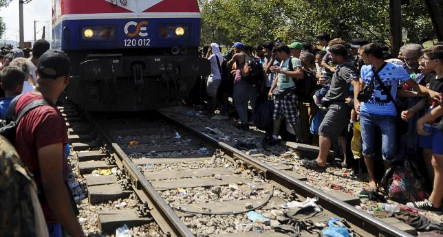 Migrants sitting along a railway track on the Greek side of the border move away as a train approaches the Greek-Macedonian border, near Gevgelija August 24, 2015. REUTERS/Ognen Teofilovski
