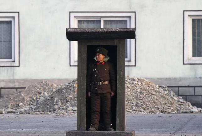 A soldier stands guard at a sentry on the banks of the Yalu River, near the North Korean town of Sinuiju, opposite the Chinese border city of Dandong