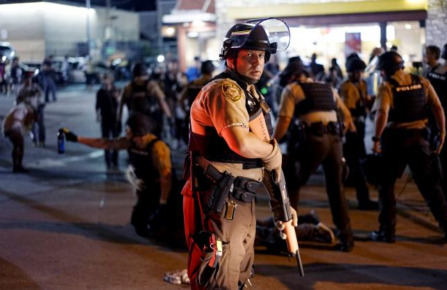 A police officer holds his weapon as a protester is detained (rear) in Ferguson, Missouri, August 10, 2015.   REUTERS/Rick Wilking