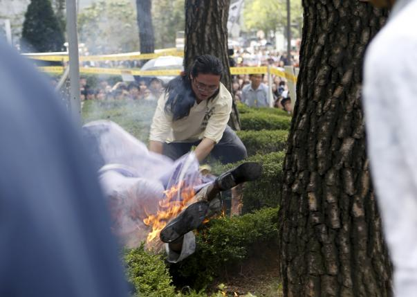 A man attempts to put out flames from another man who set himself on fire during a weekly anti-Japan rally in Seoul