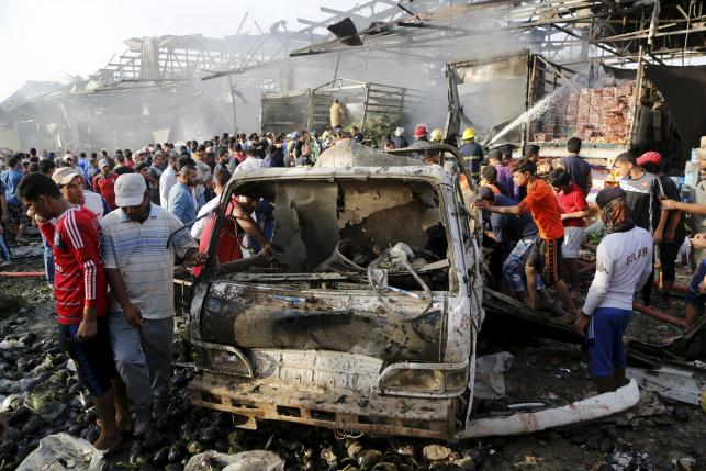 Residents gather at the site of a truck bomb attack at a crowded market in Baghdad ,August 13,2015.  REUTERS/Wissm Al- Okili