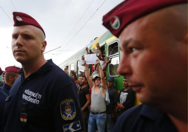 Hungarian policemen stand in front of a train with migrants at the railway station in the town of Bicske, Hungary, September 3, 2015. REUTERS/Laszlo Balogh