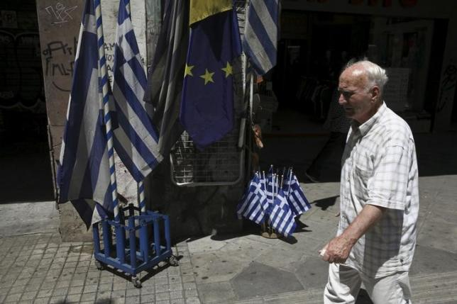 A man walks past Greek national flags and European Union flags on display outside a shop in central Athens