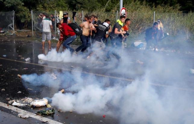 A migrant protest in a megaphone as Hungarian riot police fires tear gas and water cannon at the border crossing with Serbia in Roszke