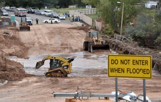 Construction equipments clear debris after a flash flood in Hildale, Utah