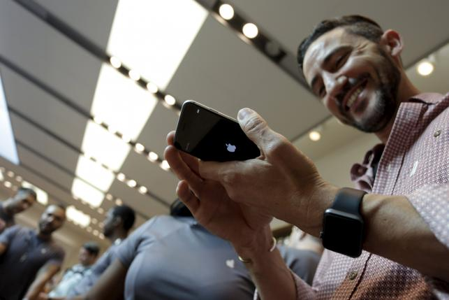 A man holds an iPhone 6 Plus as the Apple iPhone 6s and 6s Plus go on sale at an Apple Store in Los Angeles, California