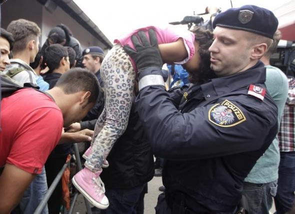 Police officer lifts up a young girl to prevent her from being crushed as migrants line-up to board trains at Austrian railway station of Nickelsdorf