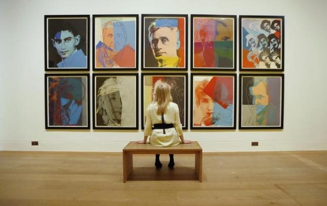 """Gallery employee Maddy Adeane poses with Andy Warhol's """"Ten Portraits of Jews of the Twentieth Century"""" (1980)  at the Dulwich Picture Gallery in London"""