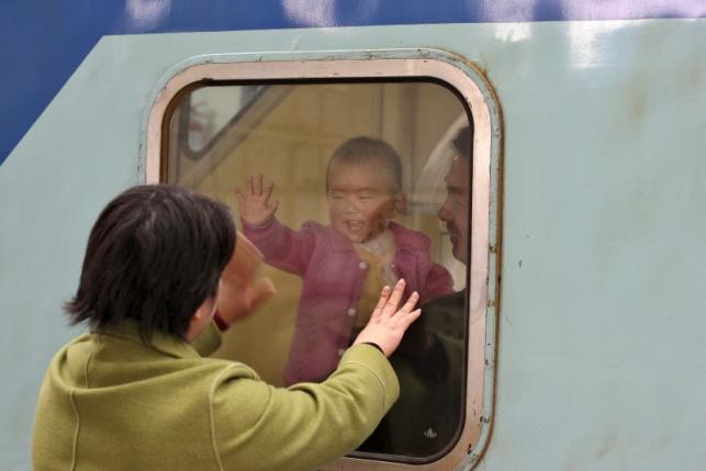 File photo of a Chinese baby waving to his mother as he and his father depart from Shanghai's train station