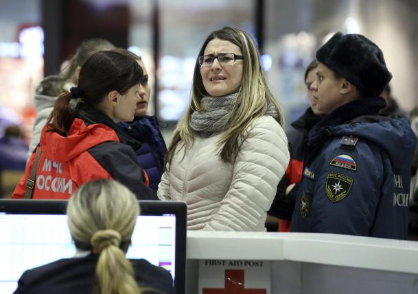 Woman reascts next to Russian Emergencies Ministry members at Pulkovo airport in St. Petersburg