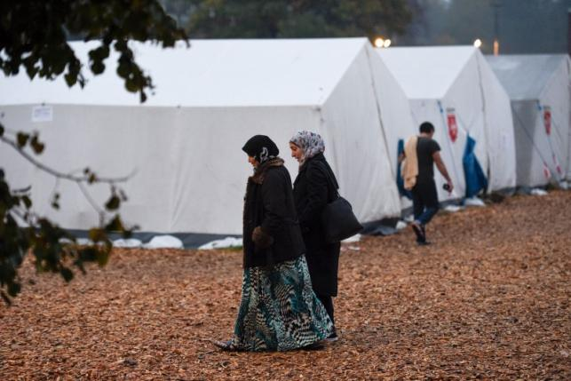 Migrants walk in front of tents in a refugee camp in Celle
