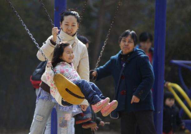 File photo of a mother pushing her daughter on a swing in Beijing