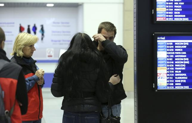 Man reacts next to Russian Emergencies Ministry members at Pulkovo airport in St. Petersburg