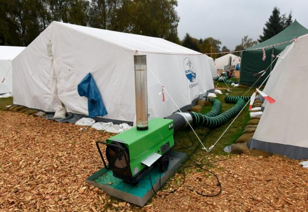 A heater is seen in front of tents in a refugee camp in Celle