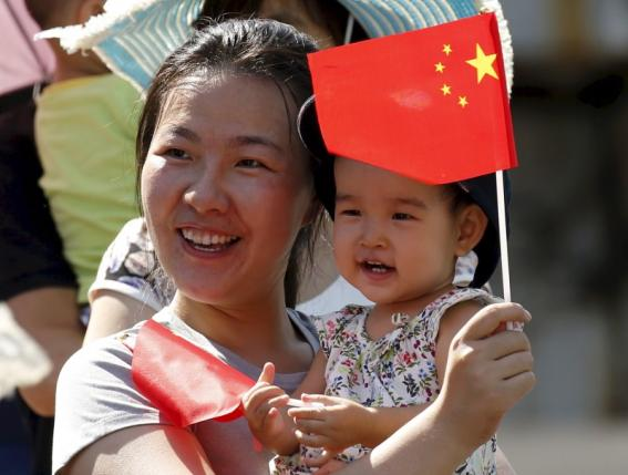 File photo of woman and her baby waiting on the street for the performance in Beijing