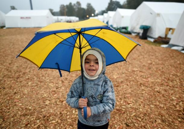 Three-year-old Yazem from Aleppo, Syria, holds an umbrella as he stands in front of tents in a refugee camp in Celle
