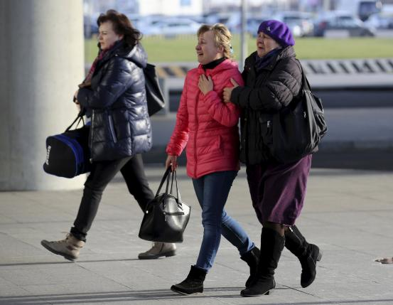 Women reacts as they walk at Pulkovo airport in St. Petersburg