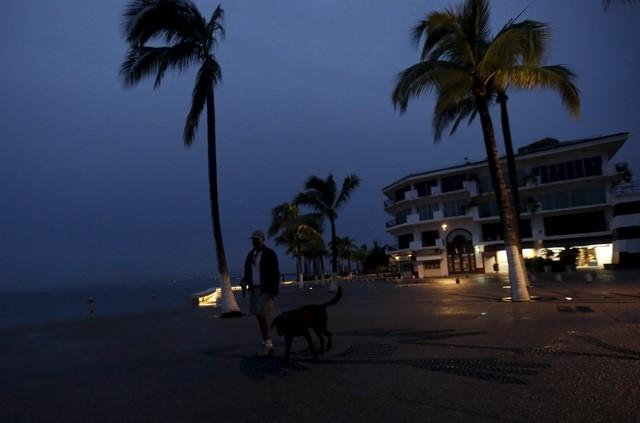 A man walks with his dog along the city's historic boardwalk as Hurricane Patricia approaches the Pacific beach resort of Puerto Vallarta, Mexico