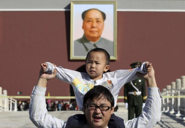 A boy sits on his father's shoulders as they pose for a photograph in front of the giant portrait of late Chinese chairman Mao Zedong on the Tiananmen Gate, in Beijing