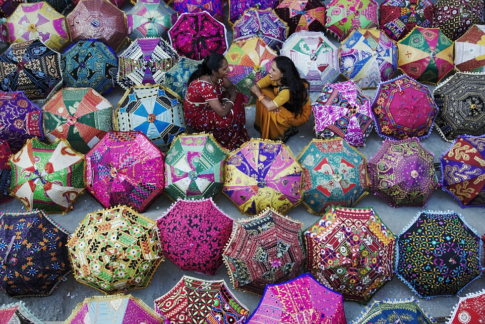 Women in sari's admiring colourful umbrellas outside a shop. Jaipur, India. Model Released. Property Released.