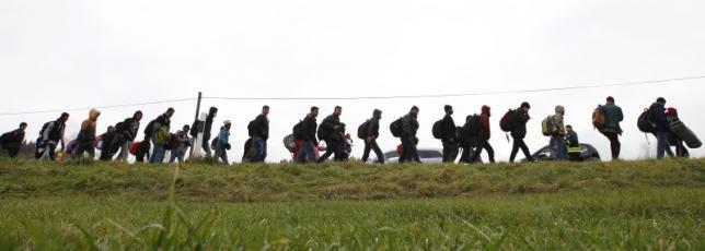 Migrants walk along street after passing Austrian-German border near Wegscheid