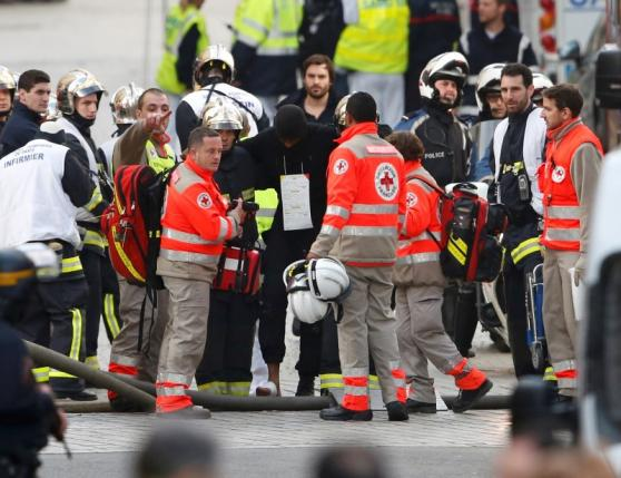 French medical rescue workers evacuate an injured member of police forces during an operation at the scene in Saint-Denis, near Paris