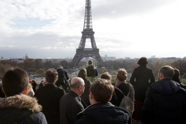 People observe a minute of silence at the Trocadero in front of the Eiffel Tower to pay tribute to the victims of the series of deadly attacks on Friday in Paris