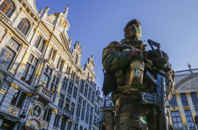 A Belgian soldier patrols in Brussels' Grand Place as police searched the area during a continued high level of security following the recent deadly Paris attacks