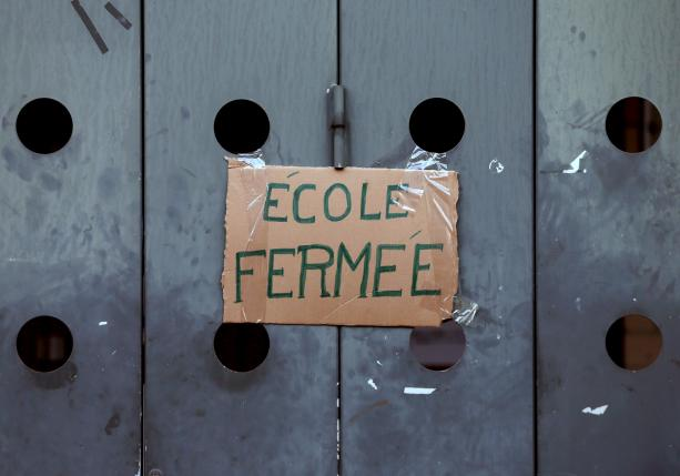 "A sign, reading  ""school closed"", is placed at the entrance of a primary and nursery school in Brussels"