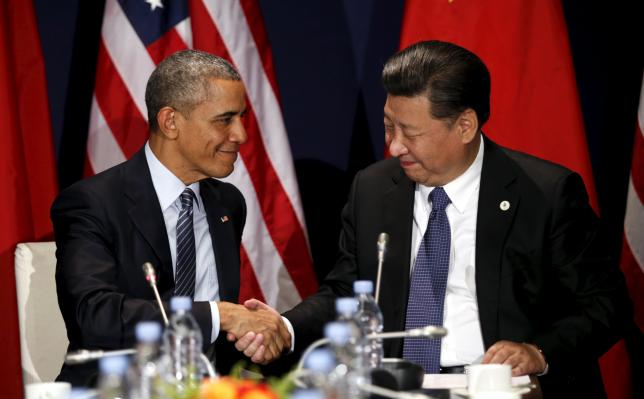 U.S. President Barack Obama shakes hands with Chinese President Xi Jinping during their meeting at the start of the climate summit in Paris