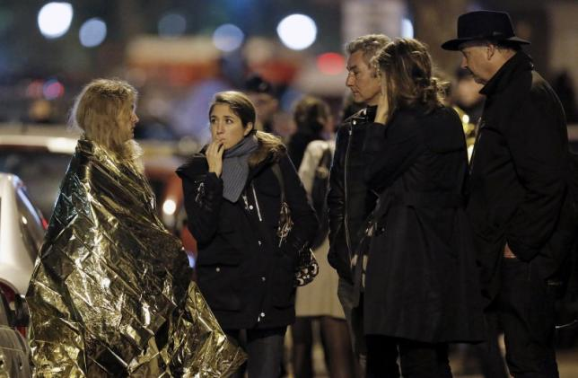 People react and keep warm using thermal blankets near the Bataclan concert hall following fatal attacks in Paris
