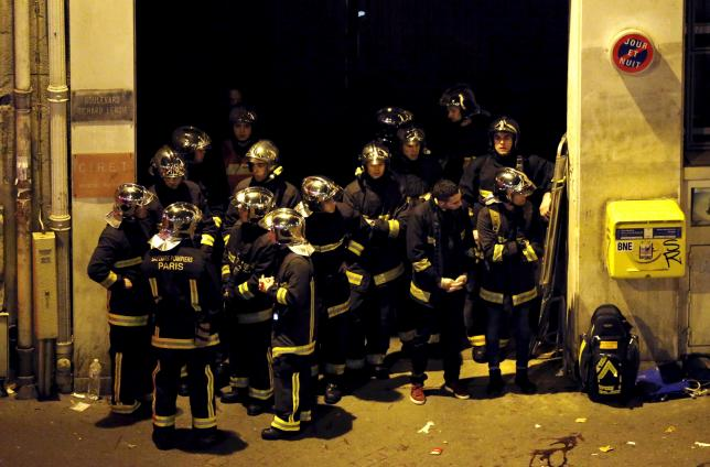 French fire brigade members gather near the Bataclan concert hall following fatal shootings in Paris