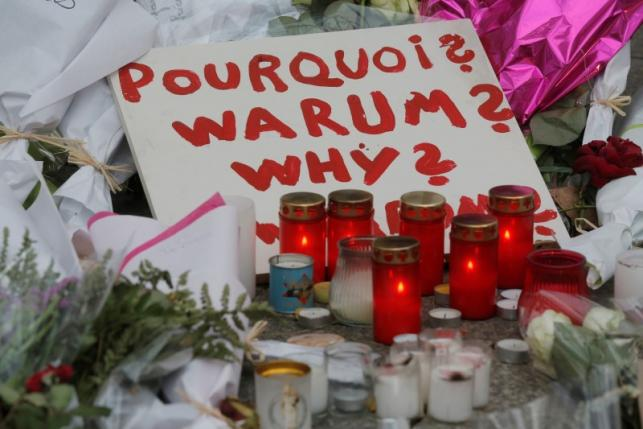 A sign asking why is seen amongst candles and flowers outside the Bataclan music hall following a series of shooting attacks on Friday in Paris