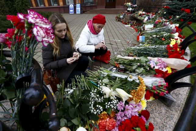 Women light candles to commemorate victims of the Paris attacks, in front of the French embassy in Minsk