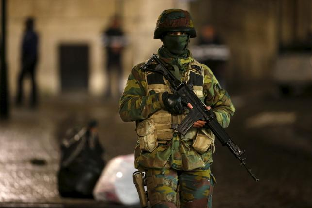 A Belgian soldier patrols along a street during a continued high level of security following the recent deadly Paris attacks, in Brussels