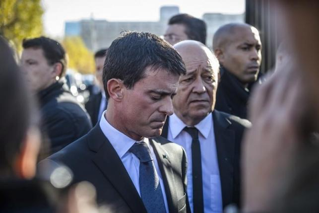 French Prime Minister Manuel Valls and French Defense Minister Jean-Yves Le Drian react as they speak to journalists after they visited the psychological help center at the Ecole Militaire in Paris