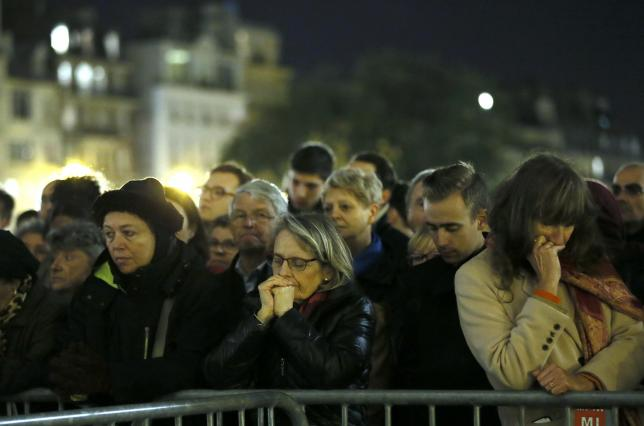 People gather outside Notre Dame Cathedral where a mass is held following a series of deadly attacks in Paris