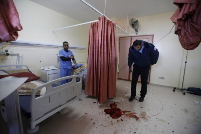 A medic looks at blood stain of a Palestinian man who was killed by Israeli undercover forces during a raid at Al-Ahly hospital in the West Bank city of Hebron
