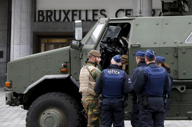 A Belgian soldier and police officers stand next to a military armoured vehicle parked at the entrance of Brussels central train station