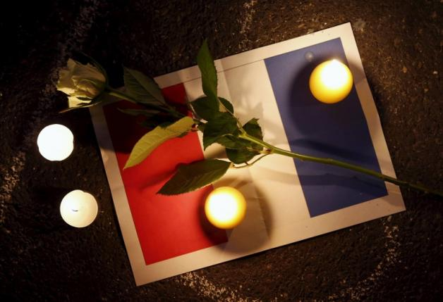 A rose is pictured on a sign depicting the flag of France next to candles during a ceremony for the victims the day after a series of deadly attacks in the French capital of Paris, in Lausanne
