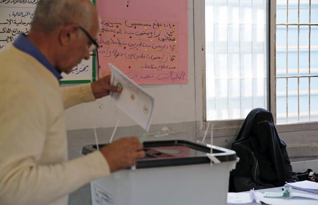 A veiled electorAn electoral worker sits near a man casting his vote at a polling station during the second round of parliamentary elections at Heliopolis in Cairo, Egypt