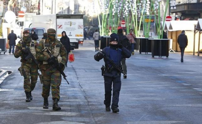 Belgian soldiers and police patrol in central Brussels as police searched the area during a continued high level of security following the recent deadly Paris attacks