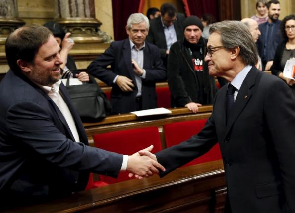 Catalan acting President Artur Mas shakes hand with ERC leader Oriol Junqueras after Catalonia's regional government voted in favor of a resolution to split from Spain at Parlament de Catalunya in Barcelona