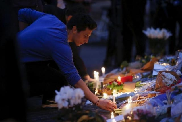 A man lights a candle for the victims of the Paris attacks in front of the French embassy in Rome