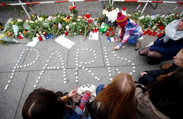 "People place candles to form the word ""Paris"" outside the French embassy in Berlin"