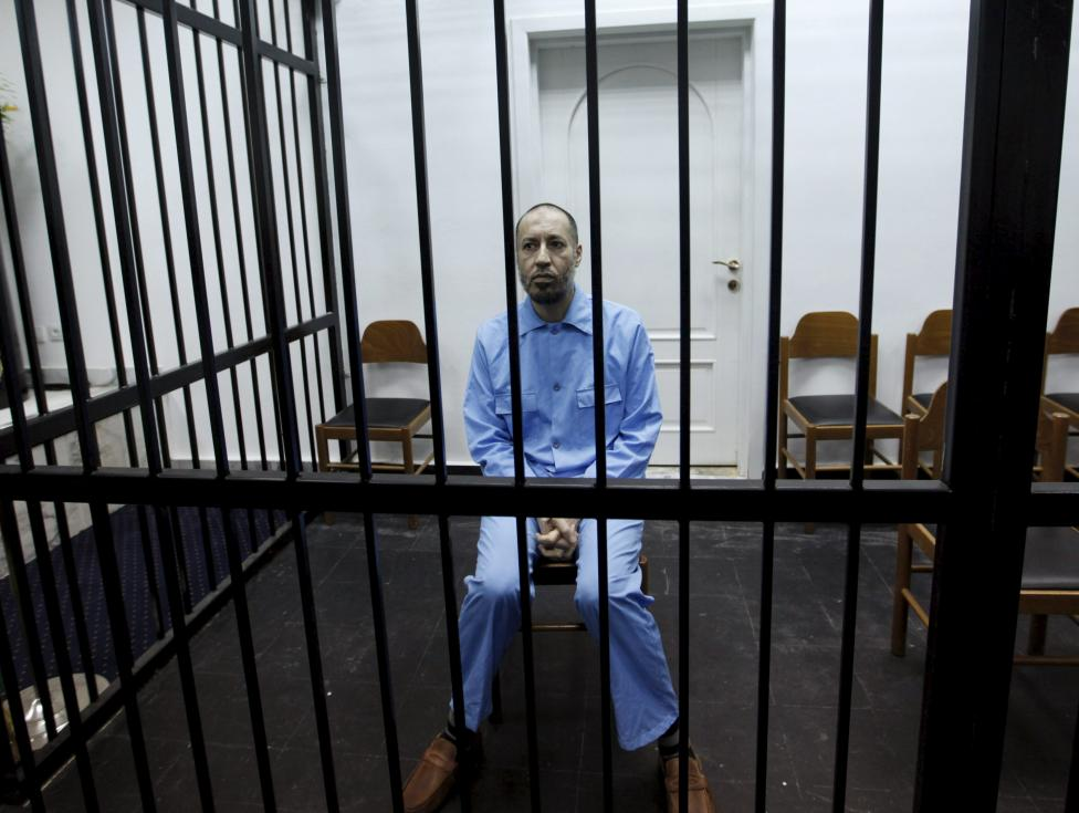Saadi Gaddafi, son of Muammar Gaddafi, sits behind bars during a hearing at a courtroom in Tripoli, Libya