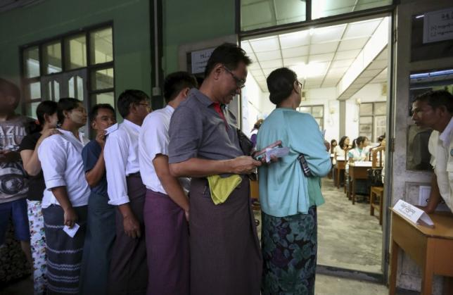 People line up to cast their votes for the general election at a polling station in Yangon