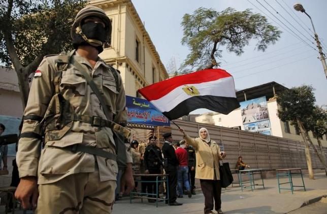 A woman waves an Egyptian national flag near a soldier standing guard outside a school used as a polling station during the second round of parliamentary elections at Heliopolis in Cairo, Egypt