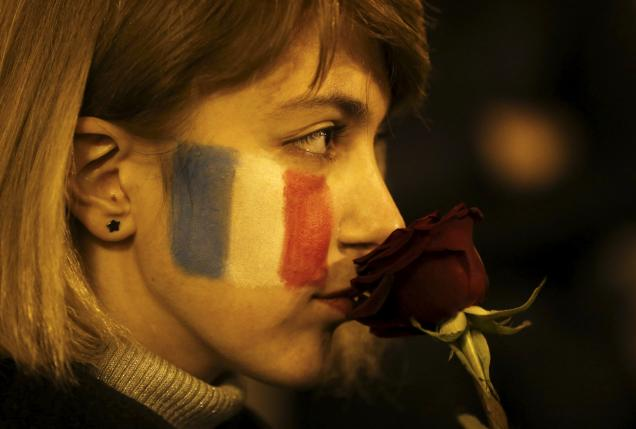A woman with French flag painted on her face, holds a flower during a gathering in tribute to the victims of Paris attacks in Tbilisi